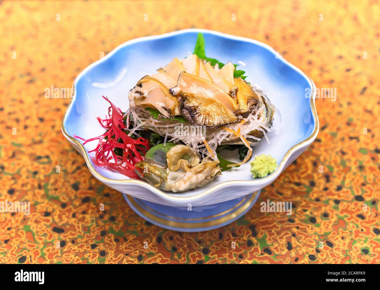 Raw sashimi high-class japanese cuisine of fresh Awabi abalone in a dish plate with Gracilaria red algae, shiso leaves and julienne of daikon radish a Stock Photo