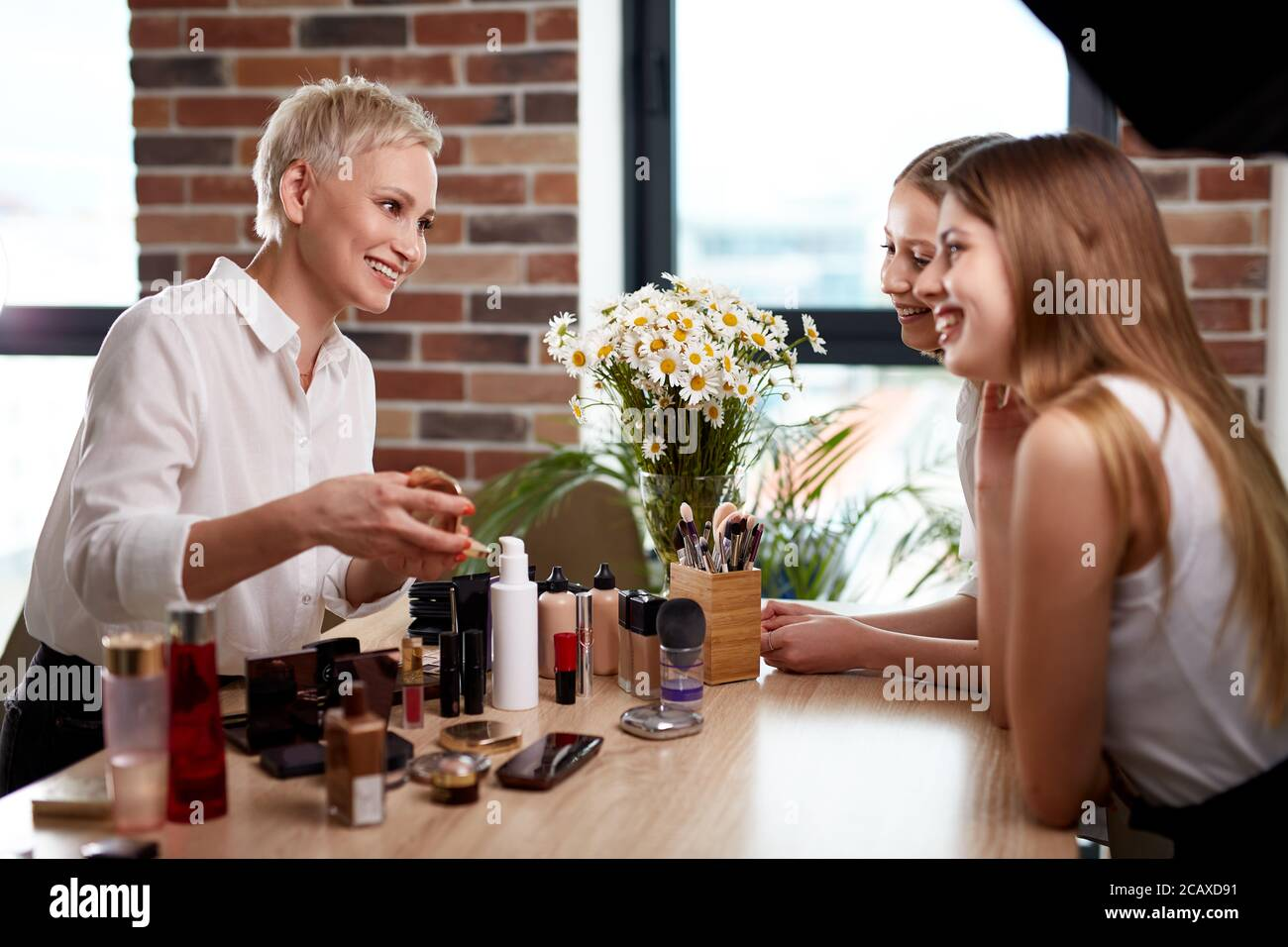 beautiful make-up artist and girls pupils discuss cosmetics on master class, professional visagist explain which of cosmetics for what is suitable for Stock Photo