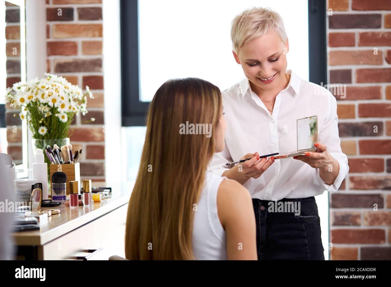 smiling adult make-up artist look at blush before applying it on face, professional visage master enjoy, loves her job Stock Photo