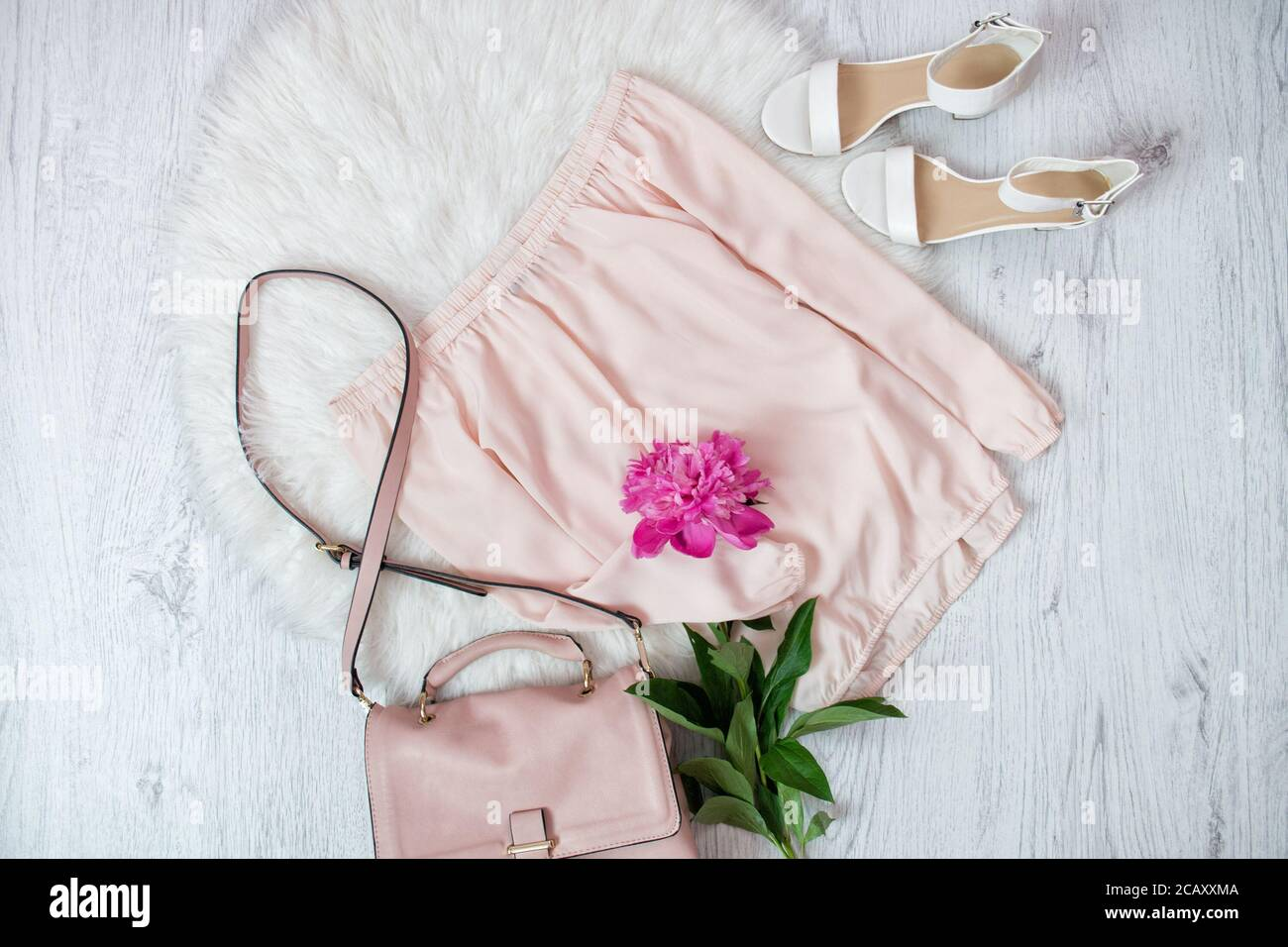 Pink blouse, bag, shoes and a peonie. Fashionable concept, white fur on the background Stock Photo