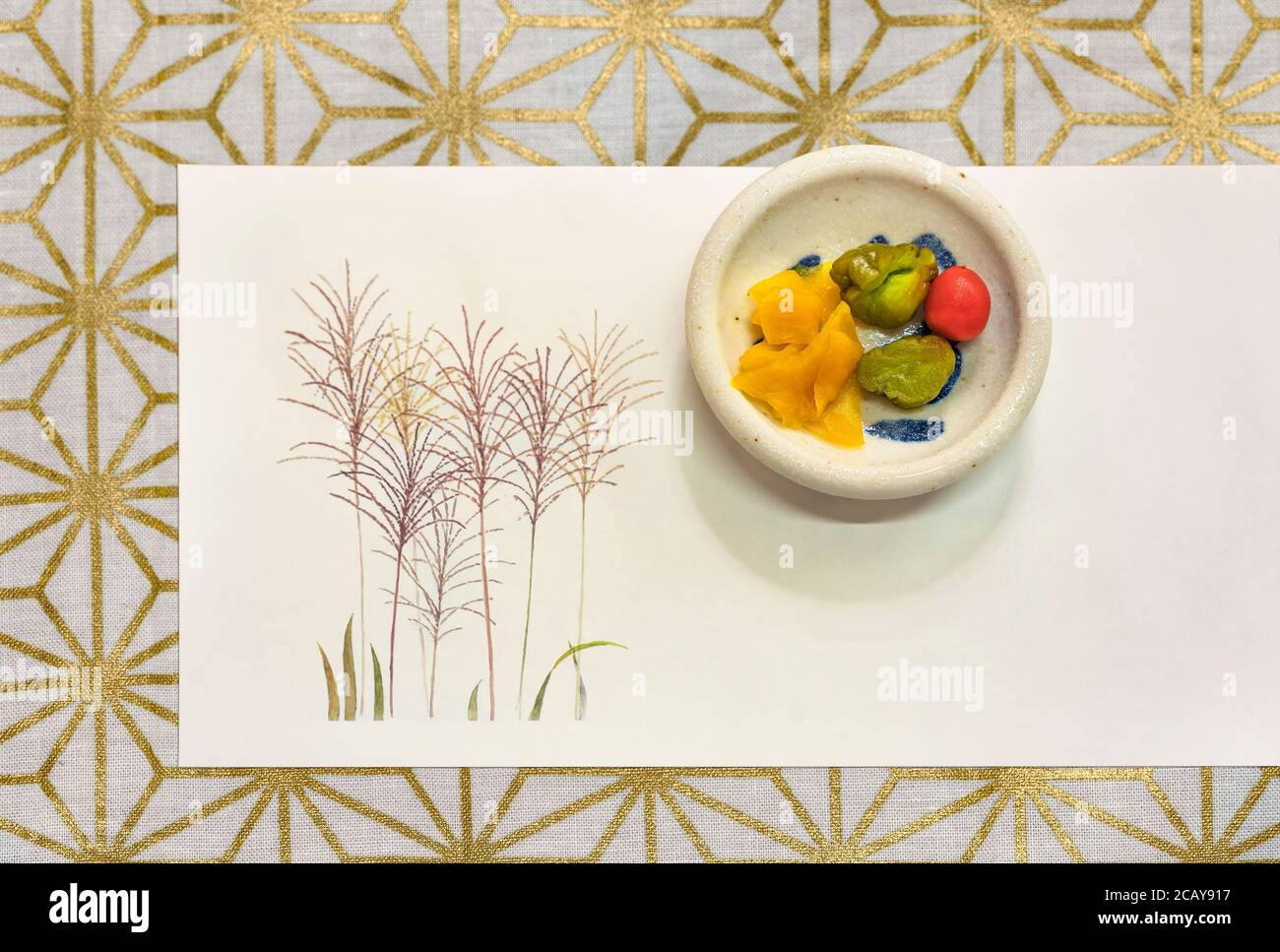 Japanese fermented tsukemono vegetables like takuan daikon radish, cucumber or karikari-koume plum on a place mat with a drawing of susuki grass and a Stock Photo
