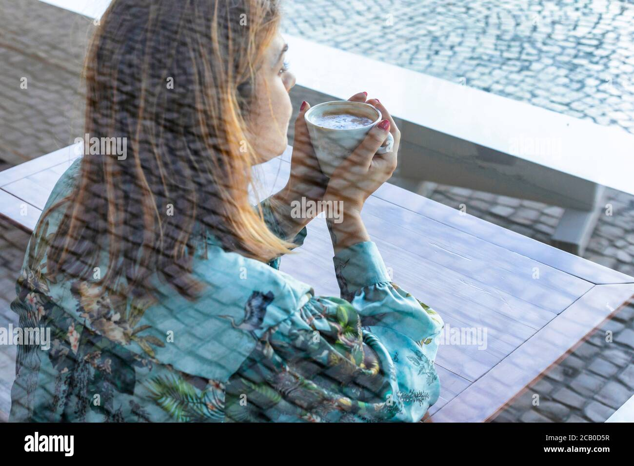 A young beautiful woman drinking a cappuccino all alone in a local coffee shop in the city of Lisbon, Portugal Stock Photo