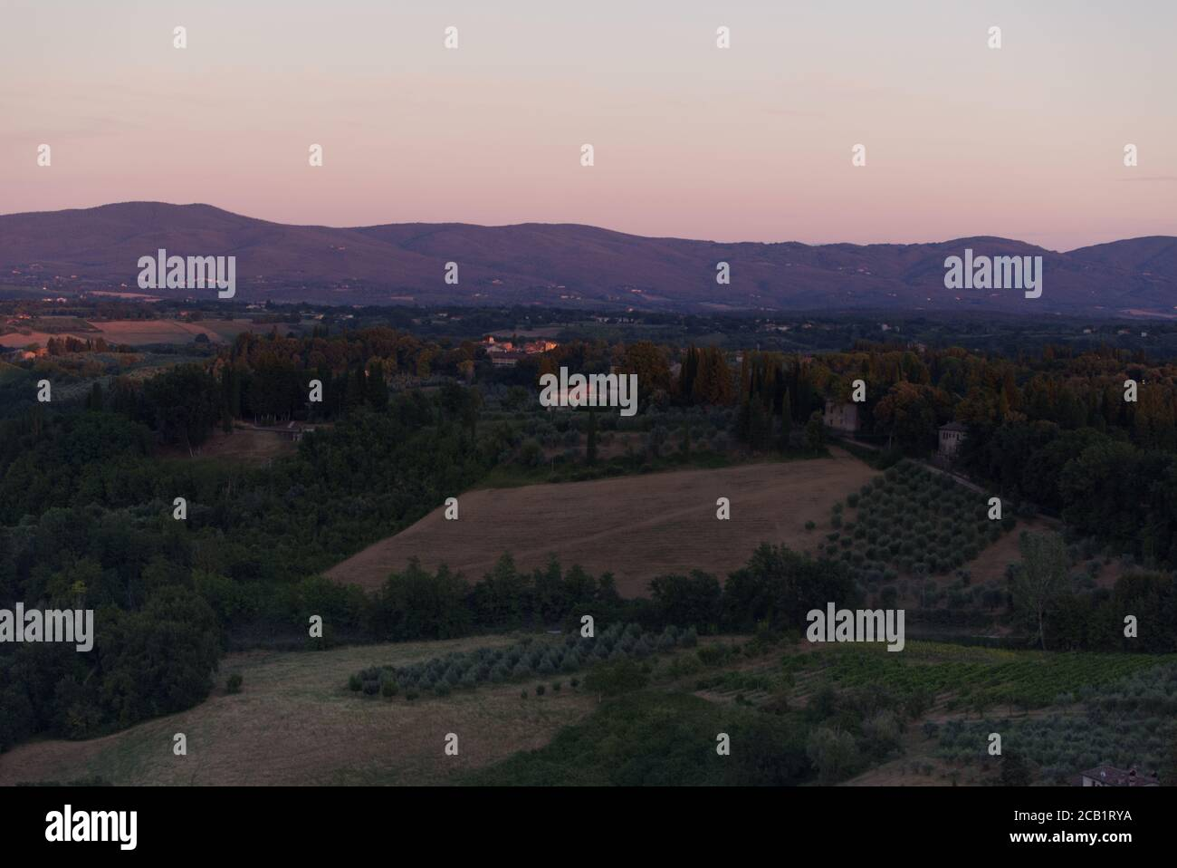 Evening lights on the Tuscan landscape, view from the town of San Gimignano Stock Photo