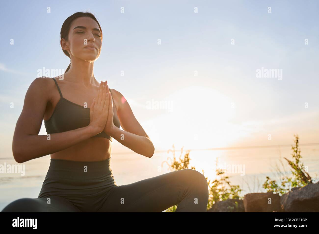 Charming young woman meditating on sunny day Stock Photo