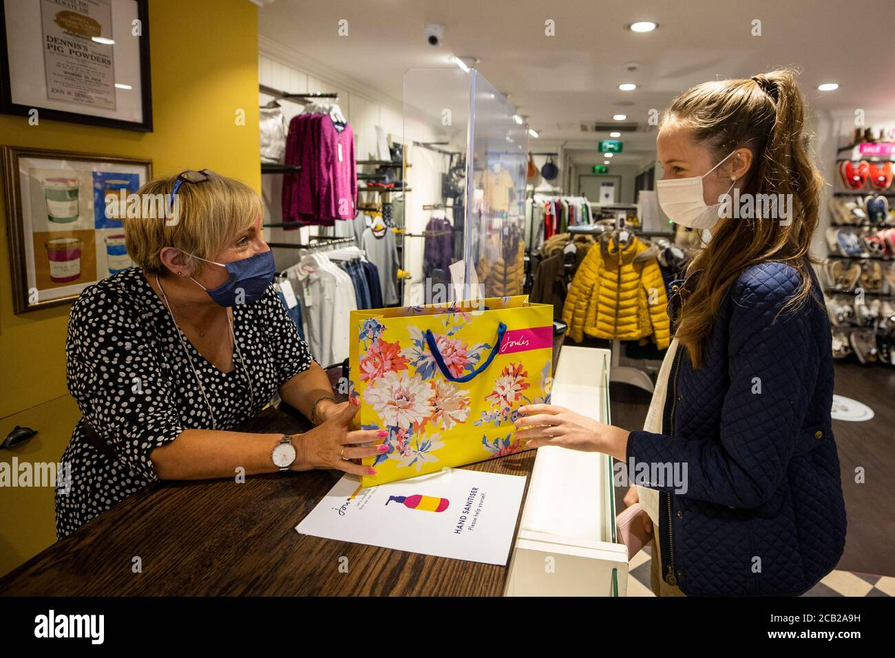 Mary Rogan Shop Assistant At Joules In Belfast Hands Ella Copper Her Purchase While Wearing A Face Mask As Face Coverings Are Now Compulsory For Shoppers In Northern Ireland Stock Photo