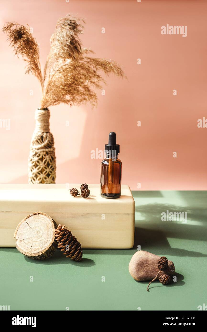 Blank amber glass essential oil bottle on wooden brick. Natural organic cosmetics, Alternative medicine, herbal essence, sustainable lifestyle concept Stock Photo