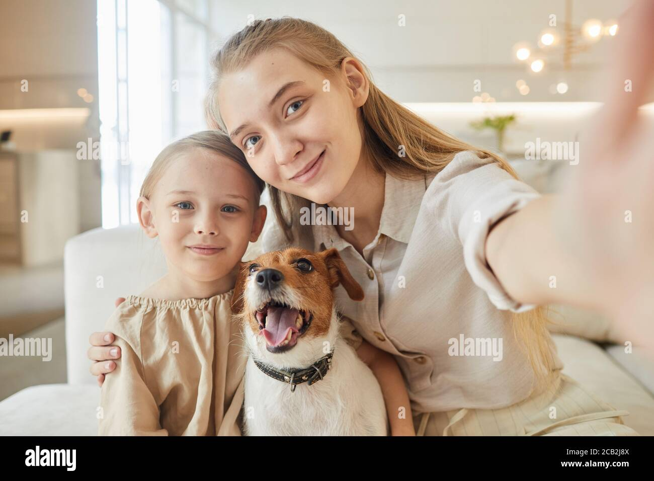 Warm-toned portrait of two sisters taking selfie with pet dog and looking at camera while sitting on couch in minimal home interior, copy space Stock Photo