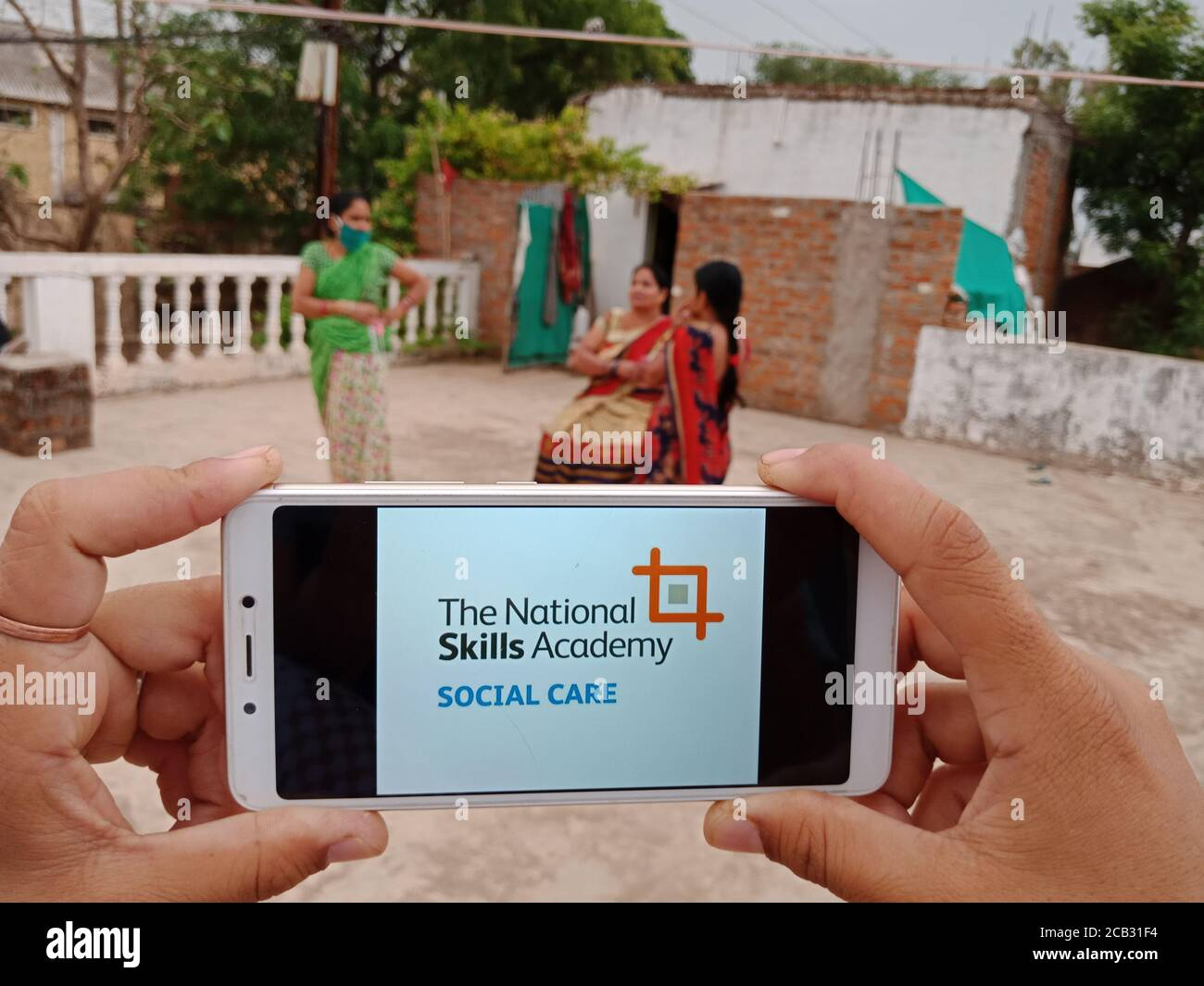 DISTRICT KATNI, INDIA - MAY 23, 2020: Woman holding smart phone with the national skills academy social care scheme on screen. Indian government rulin Stock Photo