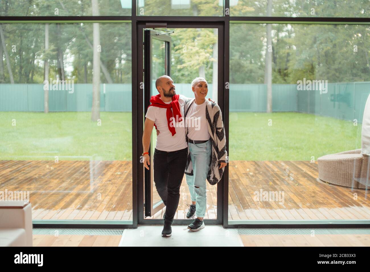 Attractive family couple entering new house, happy to spend time here. Background big panoramic window Stock Photo