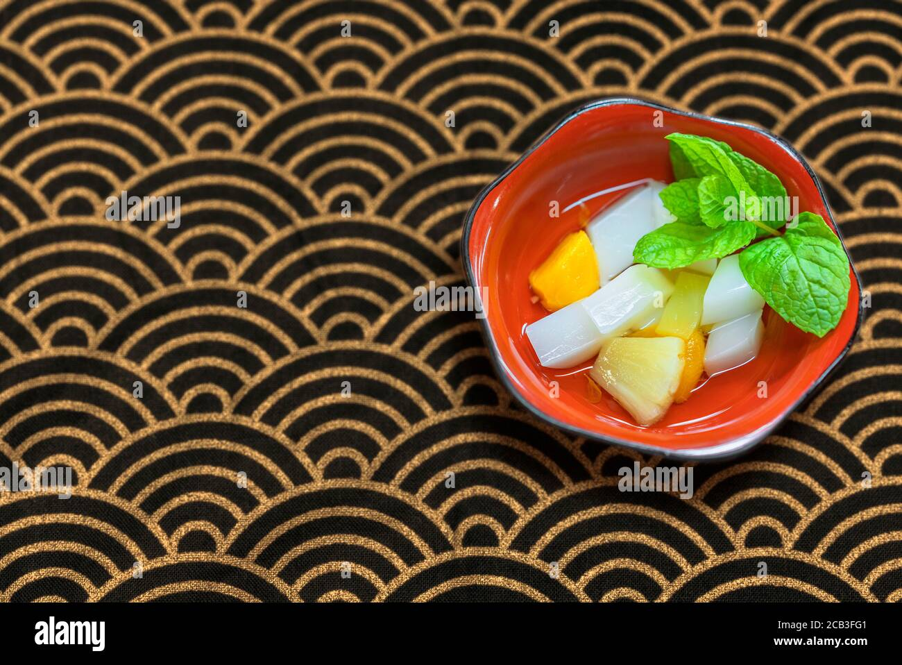 Japanese traditional dessert of Annin tofu or almond tofu made of apricot kernel milk, agar, and sugar with fruits pieces like pineapples and apricot Stock Photo