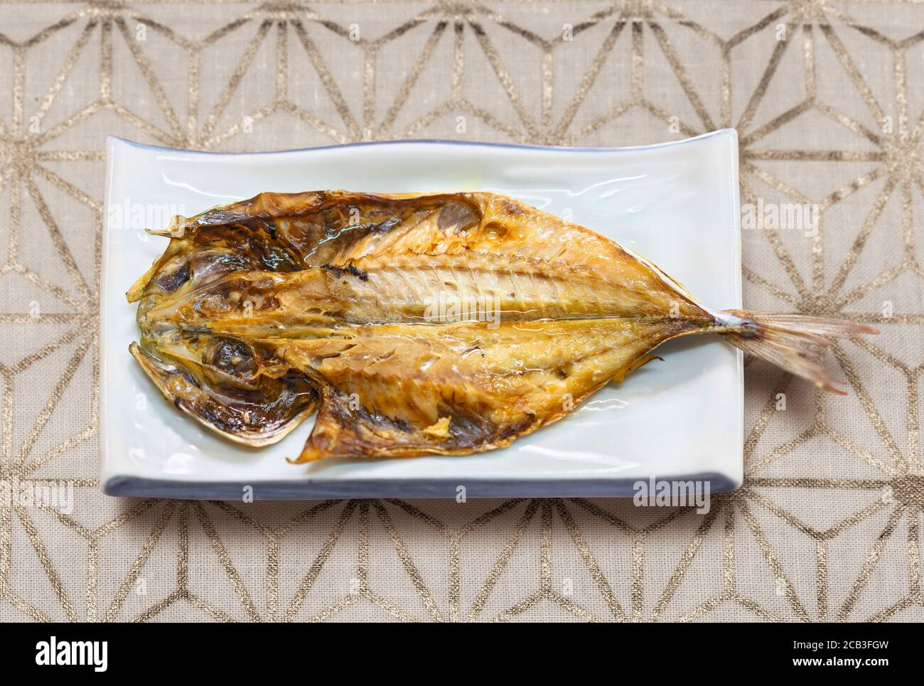 Japanese traditional grilled fish on a flower hemp leaf silver pattern table cloth. Stock Photo
