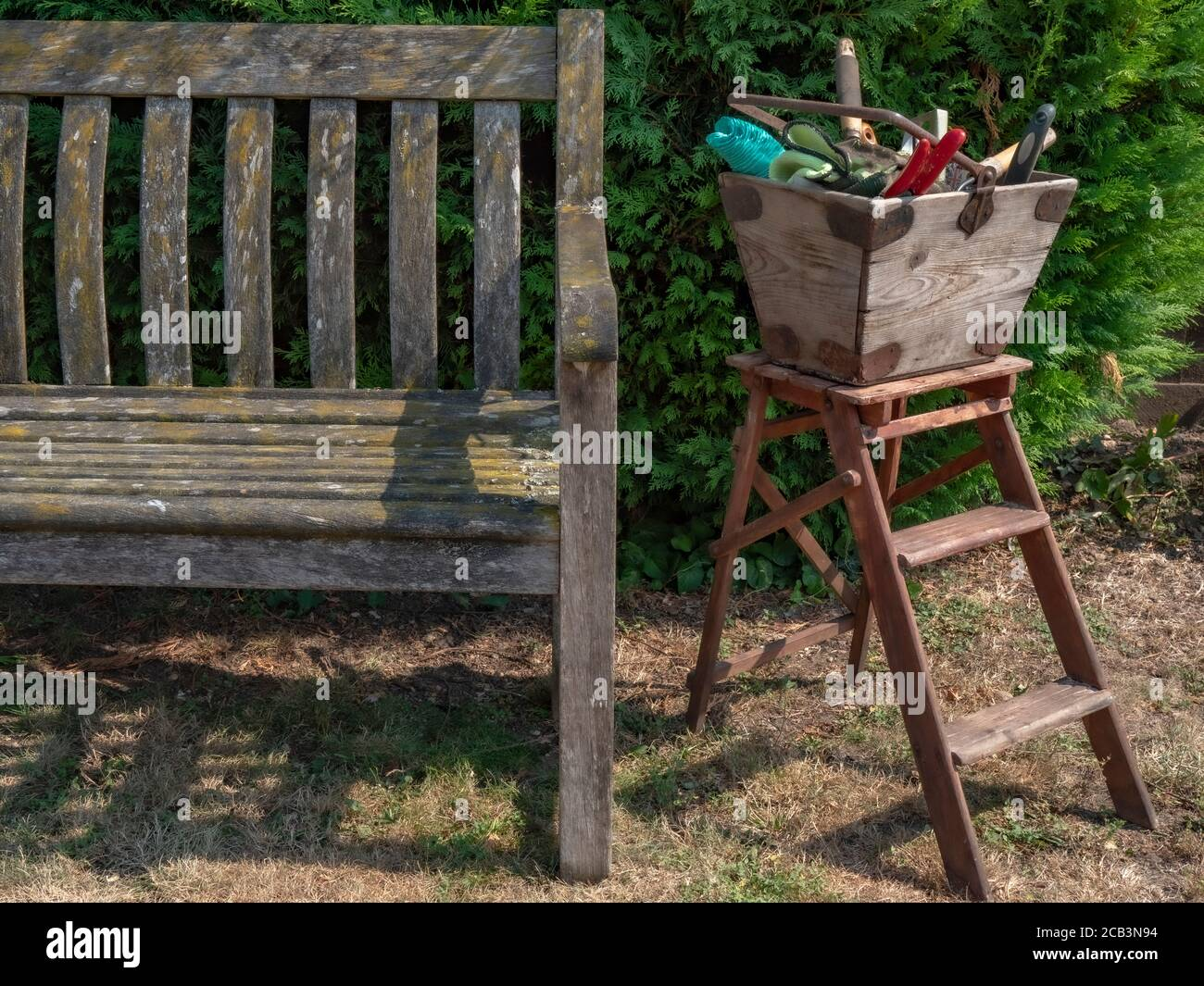 Old wooden garden tools box, holding a variety of gardening implements, on top of a small stepladder, next to an old wooden bench, in a garden / yard. Stock Photo