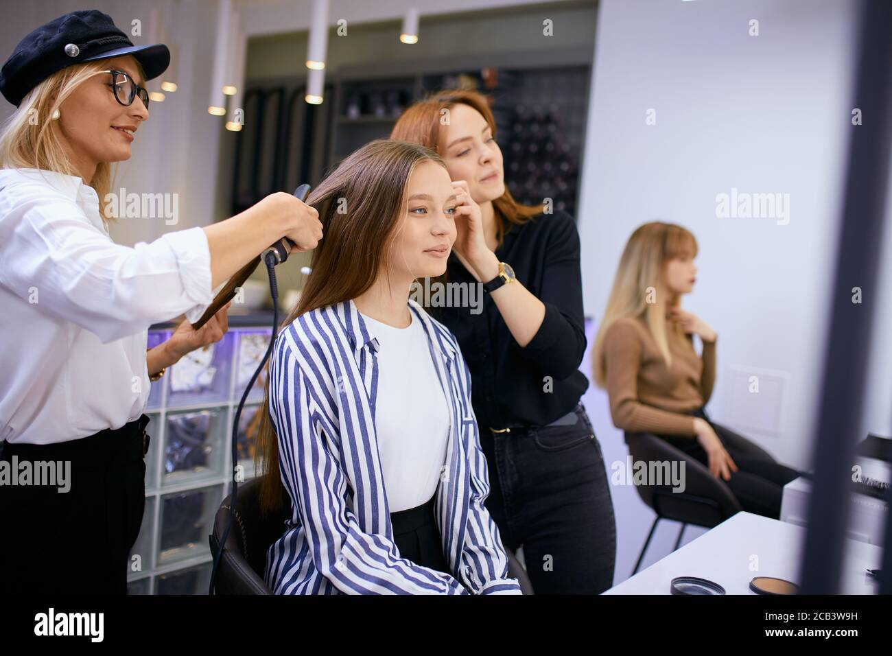 fashionable modern make-up artist doing makeup to young caucasian girl while hairdresser making hairdo in the background. Isolated in beauty saloon Stock Photo