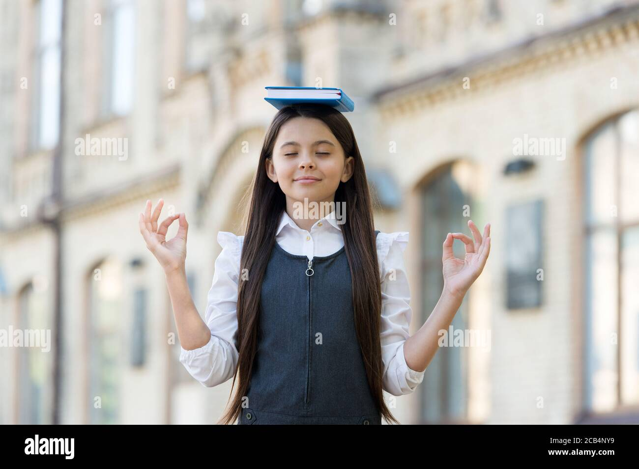 Calm the mind. Little child do meditation outdoors. Small girl do mudra hands holding book on head. Meditation for mental balance. Meditation course for beginner. School and education. Best therapy. Stock Photo
