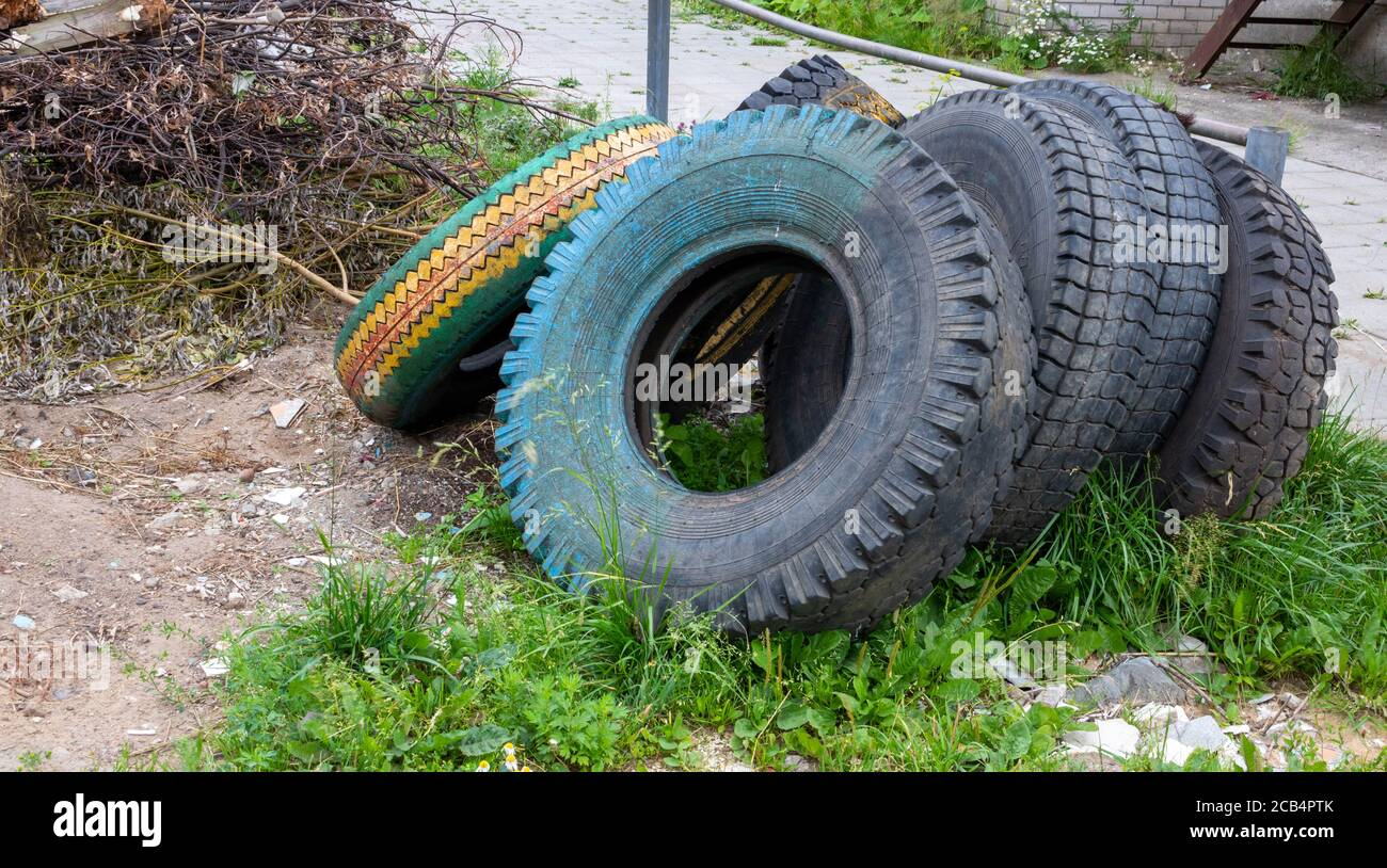 Old dirty tires are lying in the trash. Concept of environment and waste recycling Stock Photo