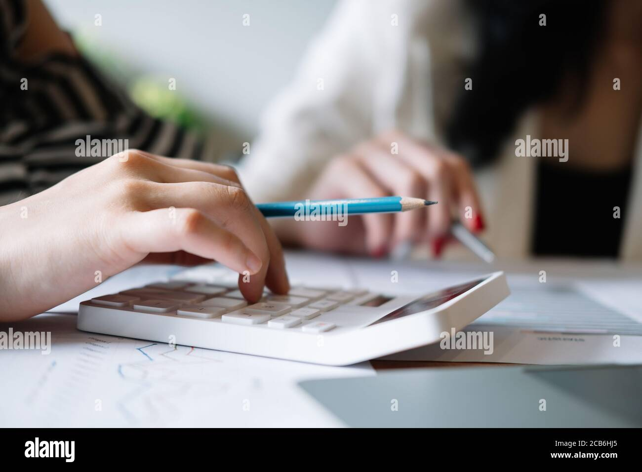 Closeup business people using calculator for calculate business data report in the office Stock Photo
