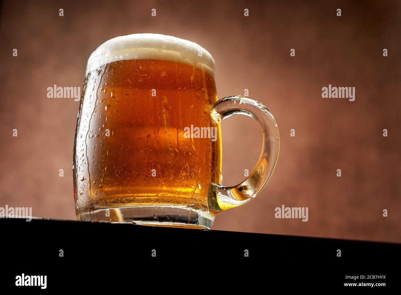 Mug of beer with foam standing against brown background Stock Photo