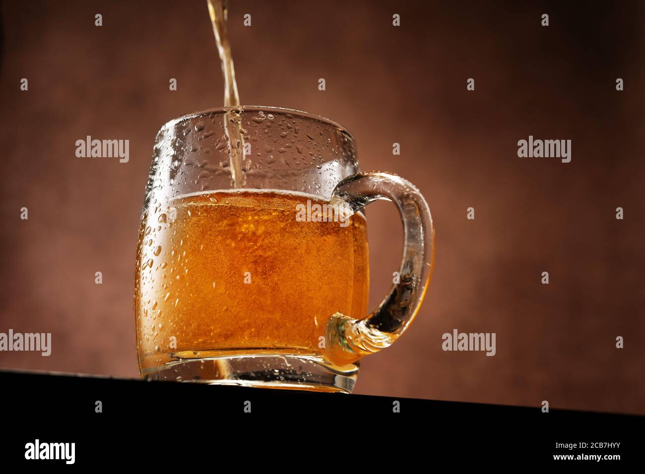Light beer beeing poured into a mug standing against brown background below the eye line Stock Photo