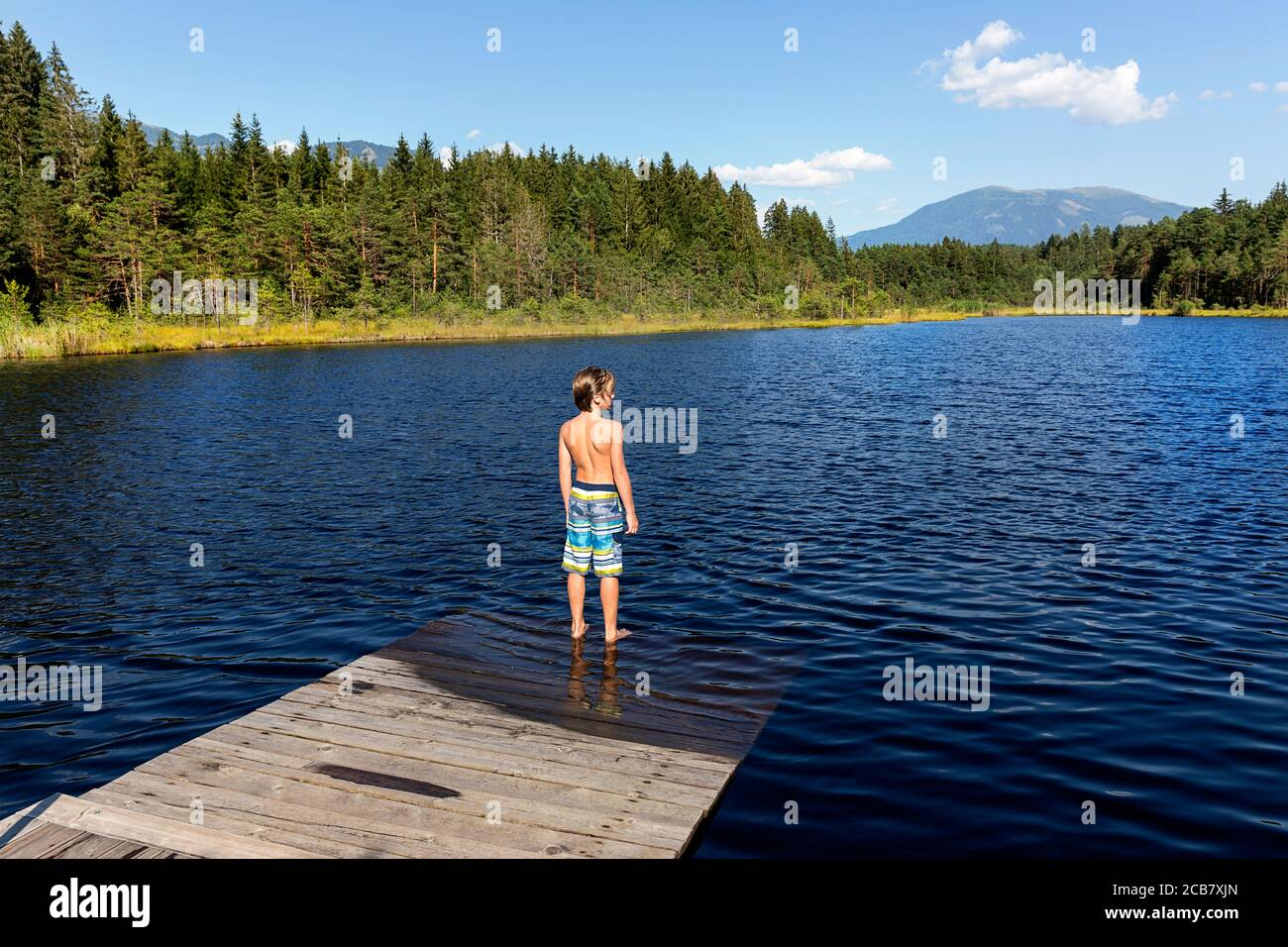 Boy standing on wooden pier in shallow water on lake Egelsee, Austria, Oberösterreich, Upper Austria Stock Photo