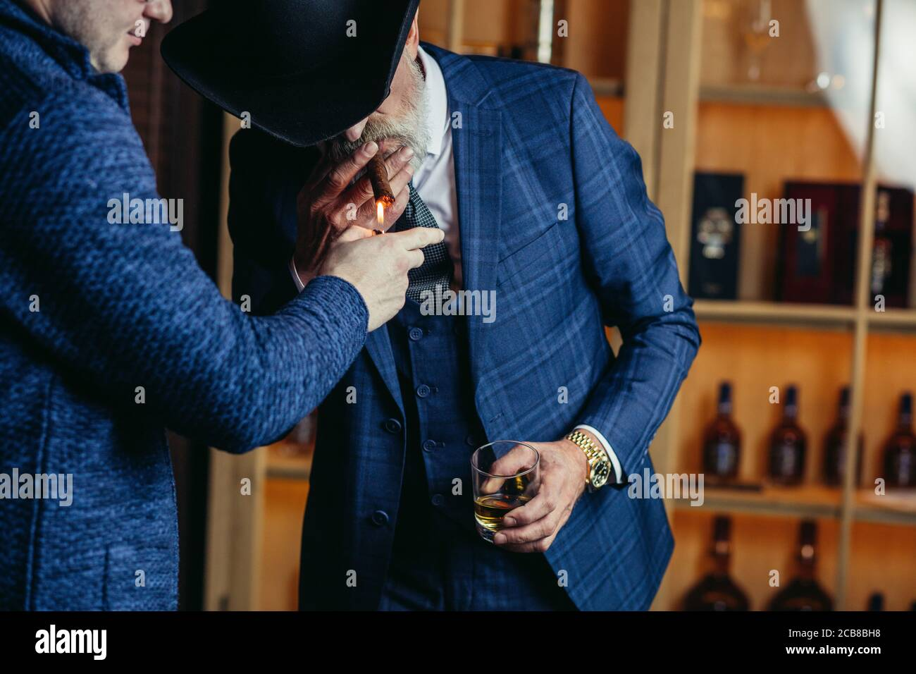 Elegant senior gentleman wearing spectacles and grey-haired beard standing at pub in wide-brimmed hat with glass of alcohol drink and cigar. Elderly m Stock Photo