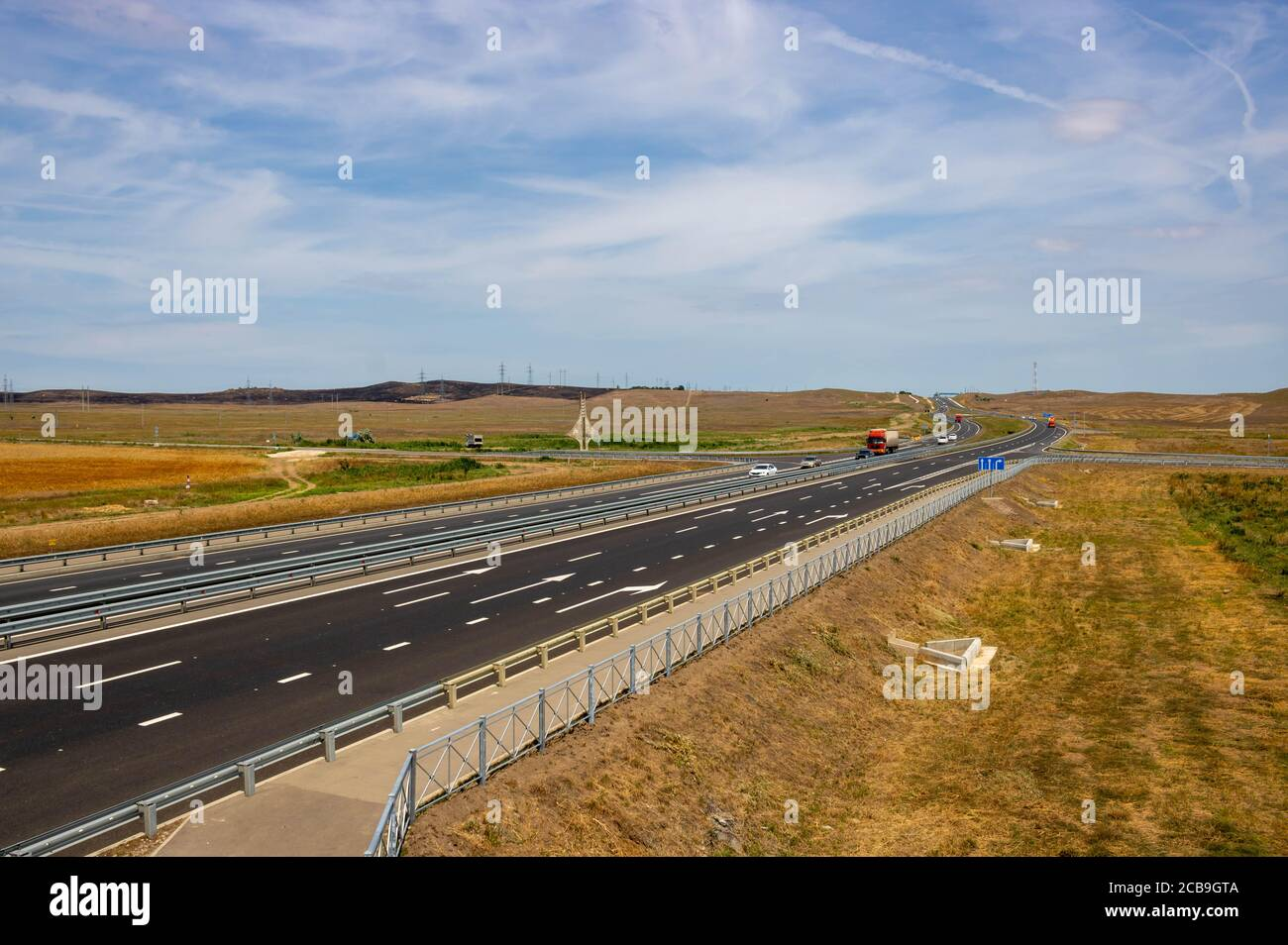 highway in steppe against a blue sky,long road stretching out into the distance. Stock Photo