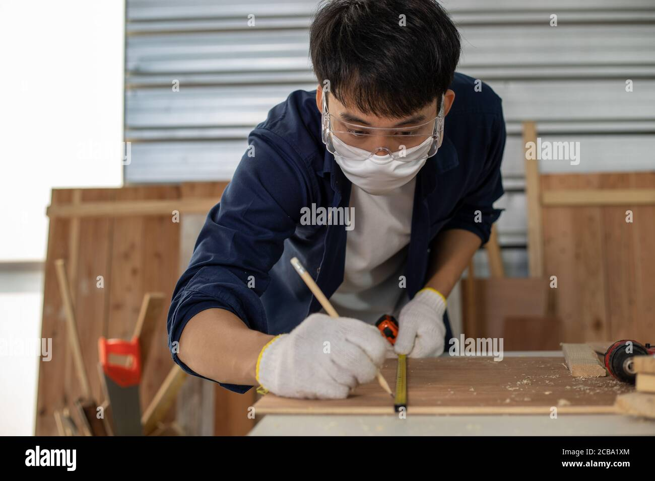 Asian man Carpenter working with technical drawing or blueprint construction paper lying on a workshop with carpentry tools and wood at home Stock Photo