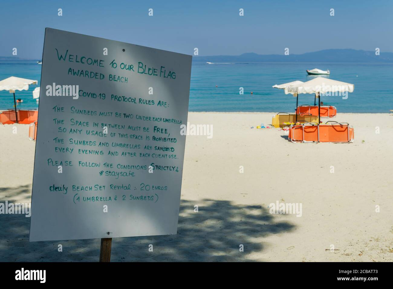 Chalkidiki, Greece Covid-19 beach precautions sign. Info at empty beach, describing protocol rules for sunbeds and umbrellas, to protect from virus. Stock Photo