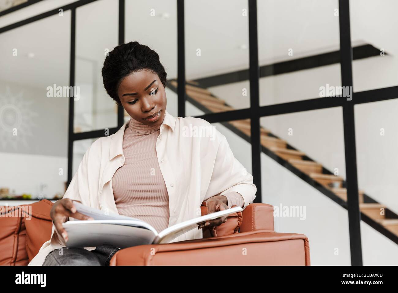 Attractive young african woman sitting on a couch at home, modern interior, reading a book Stock Photo