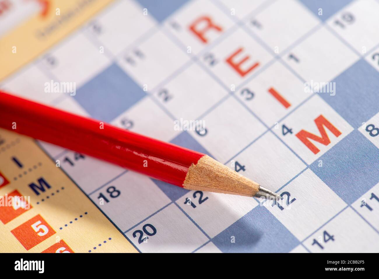 red pencil lies on crossword puzzle Stock Photo