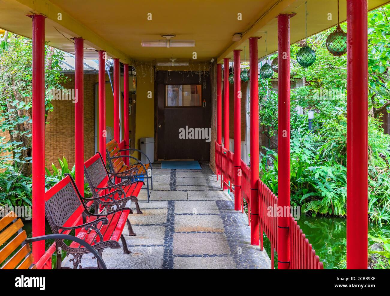 chiba, japan - july 18 2020: Hallway leading through the garden pond of a ryokan guesthouse to onsen hot spring surrounded by benches, pillars and jap Stock Photo