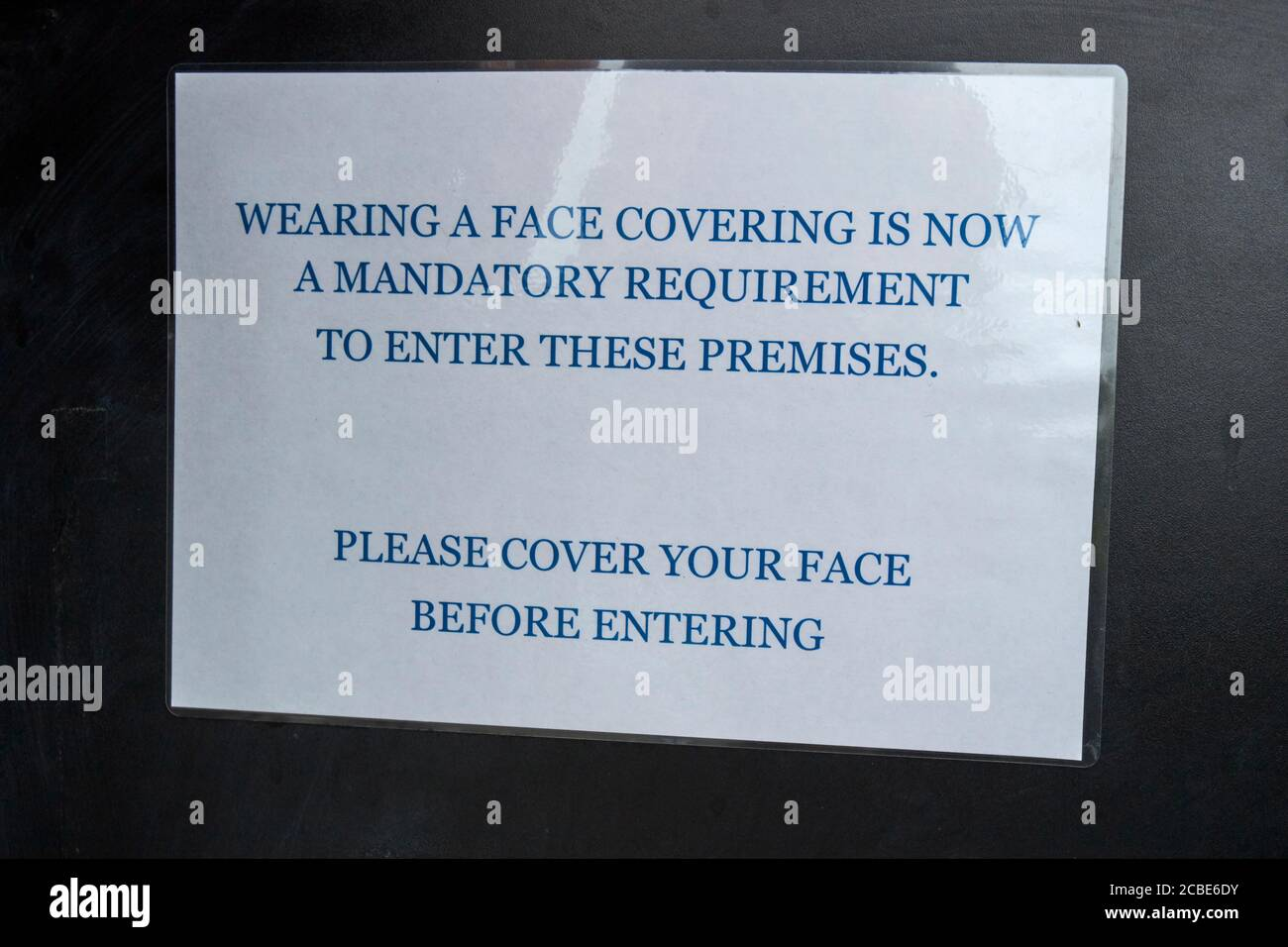 temporary notice about wearing face masks in a shop during the covid-19 coronavirus outbreak in the lake district cumbria england uk Stock Photo