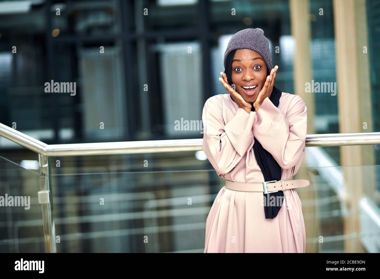 Cheerful surprised young Muslim woman of african ethnicity dressed in pink long dress and black scarf posing in urban setting smiling at camera Stock Photo