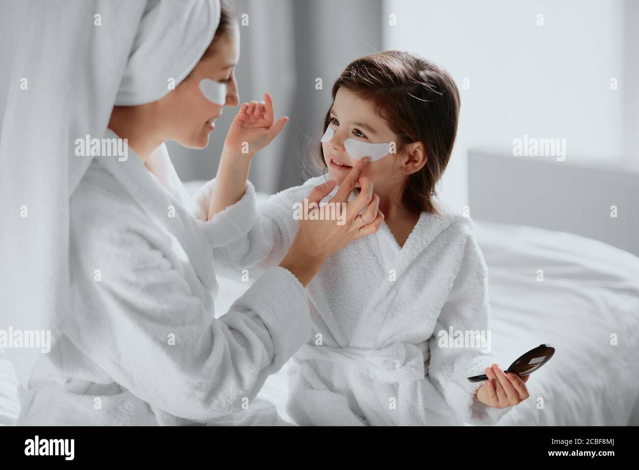 beauty concept. careful attentive mother use patches for eyes and her daughter in mask too. parents and children interested in beauty procedures Stock Photo