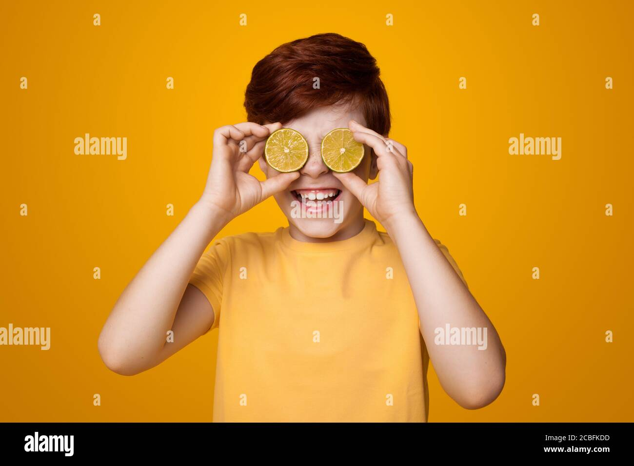 Happy ginger boy covering his eyes with lemons and smile on a yellow studio wall Stock Photo