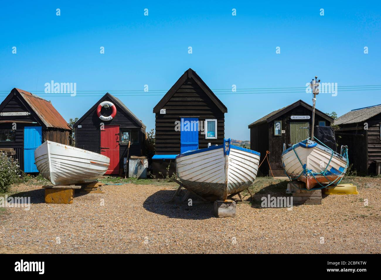 Suffolk coast UK, view in summer of fishing boats and fishermen's huts sited on the beach in Southwold harbour, Suffolk, England, UK Stock Photo