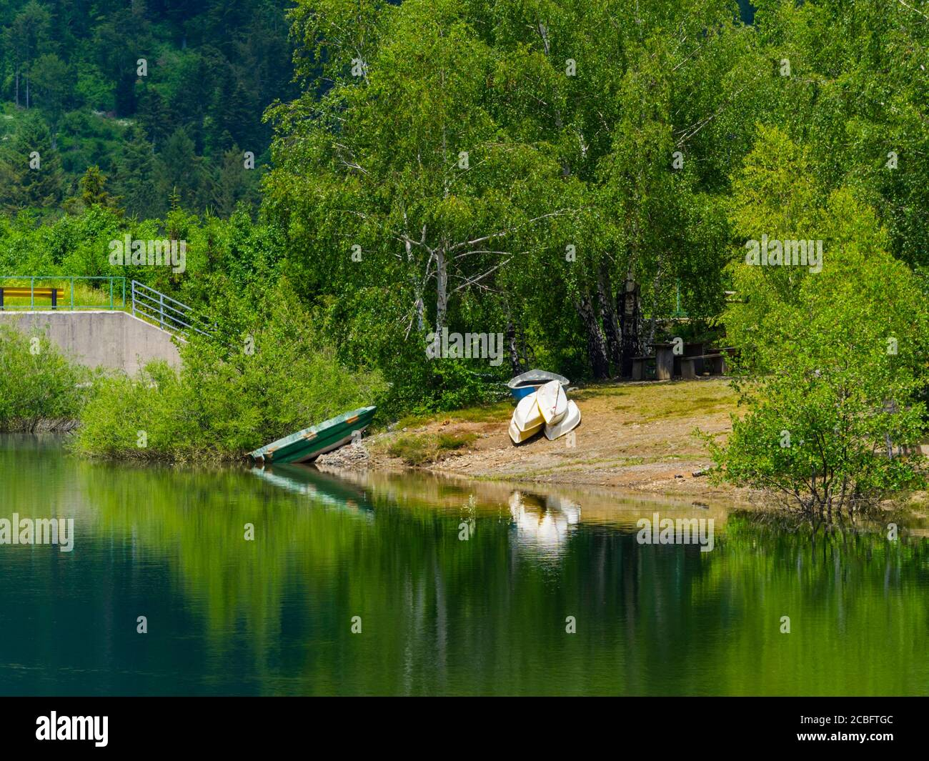 Inverter boats ashore Green forest pretty beautiful preserved nature natural environment Spring season lake Lepenica near Fuzine in Croatia Europe Stock Photo