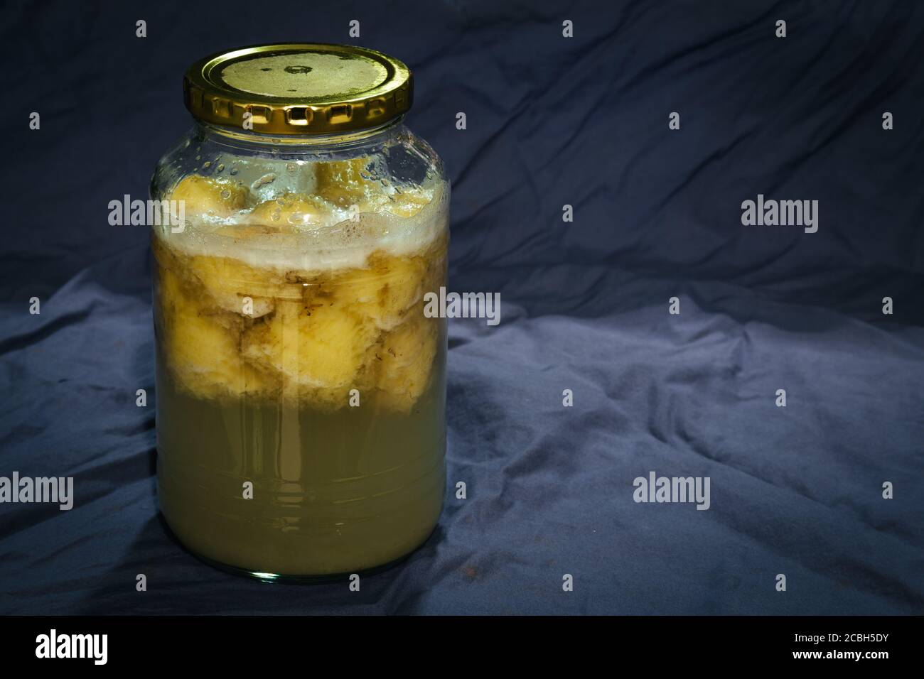 Homemade banana fruit wild natural yeast water with bubbles, active and fermenting in a glass jar Stock Photo