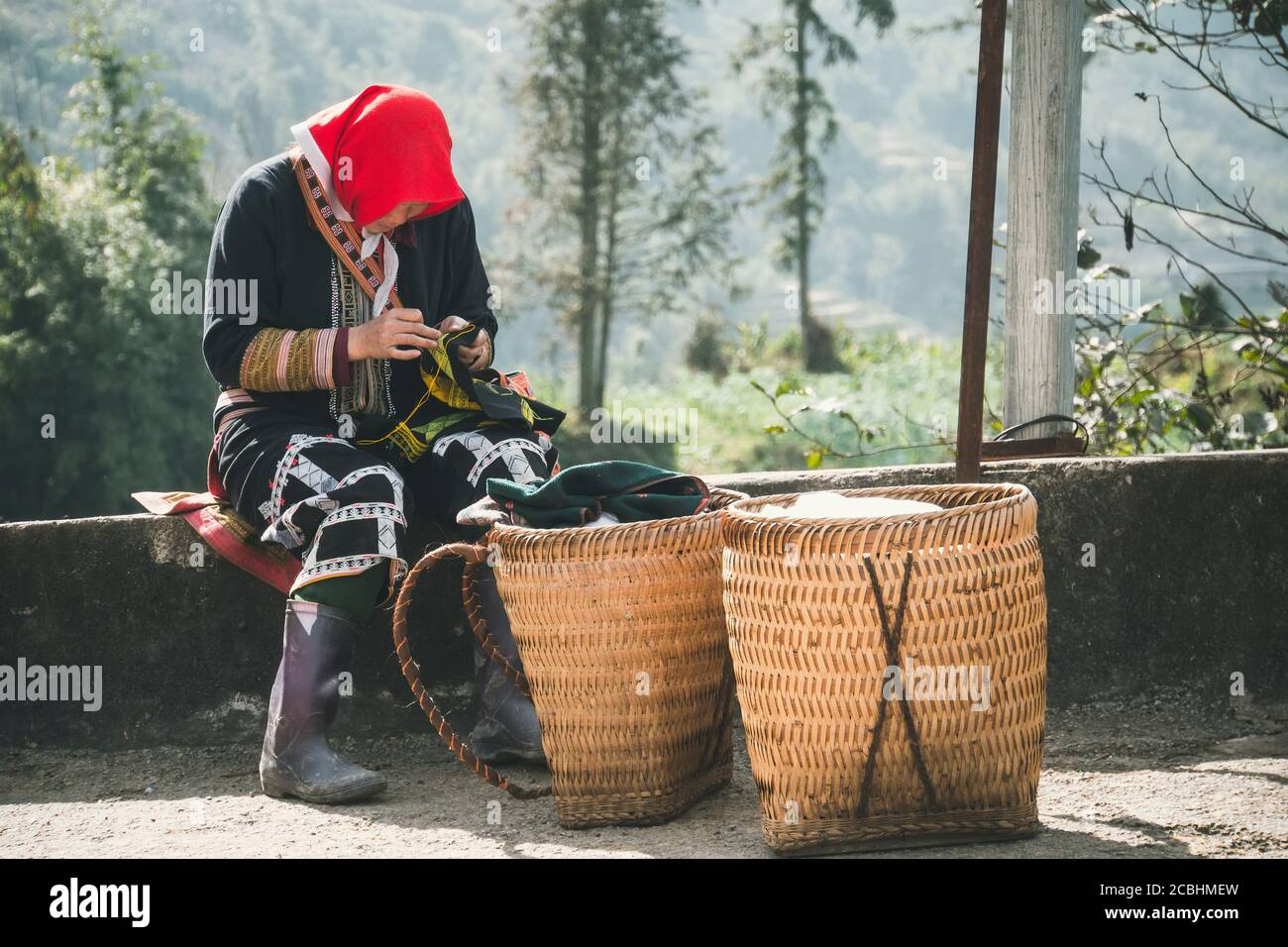 TA PHIN, LAO CAI, VIETNAM - 12 January 2019: Unidentified Red Dao little girl sews in the street. Red Dao is one of the minority ethnic groups in Stock Photo