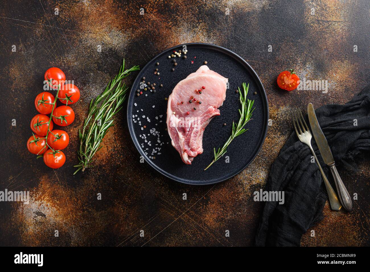 Pork belly Farm fresh , cutlet in round black modern plate on a old rustic dark metall surface rosemary garlic peppercorns top view space for text Stock Photo