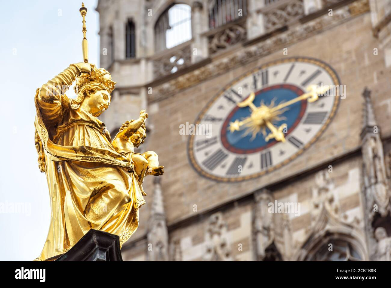 Virgin Mary statue closeup in Marienplatz square, Munich, Germany. This place is a top landmark of Munich. Golden sculpture atop Mariensaule column on Stock Photo