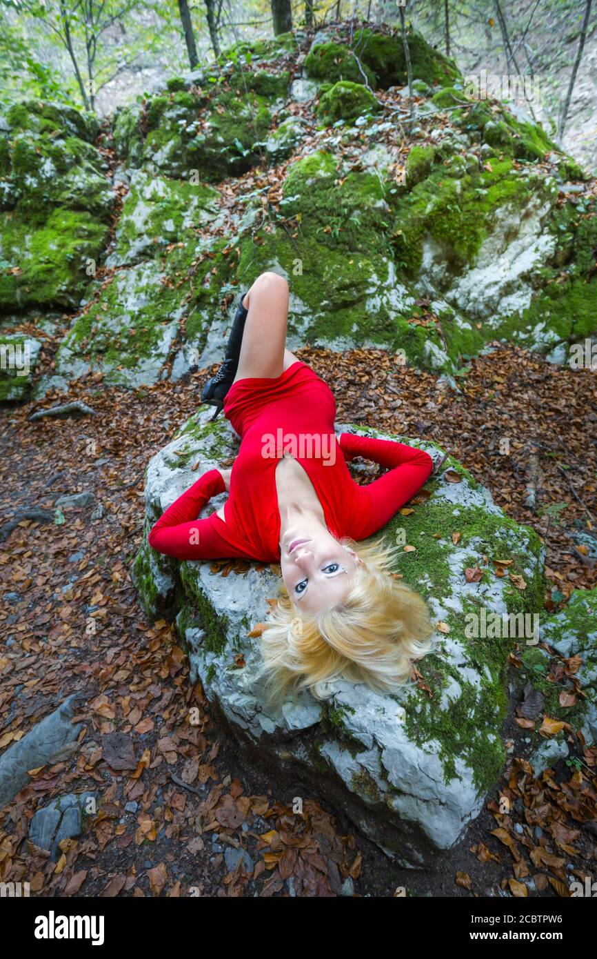 Pretty blonde young woman dressed in Red minidress in forest nature Stock Photo