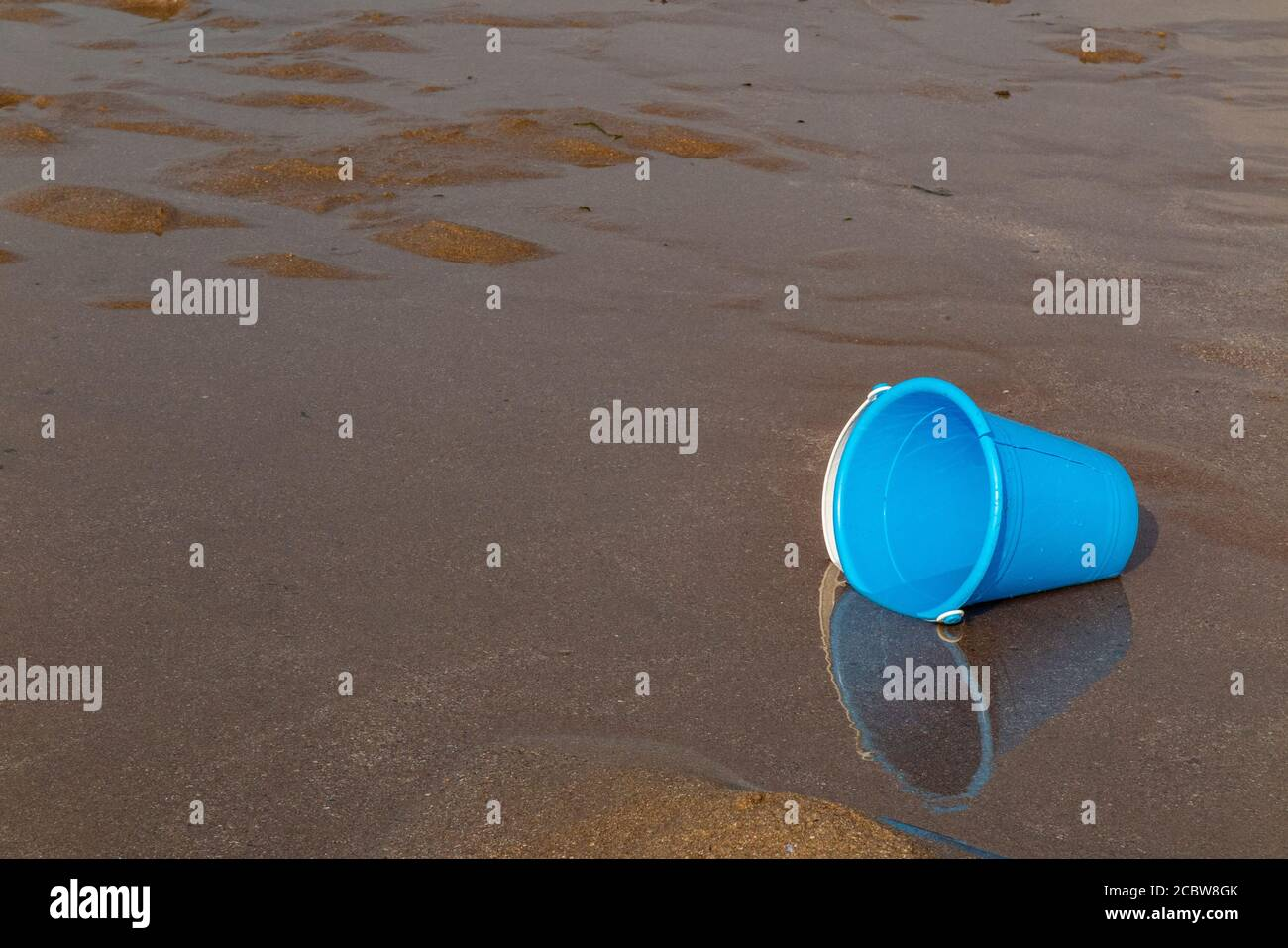 A child's plastic bucket abandoned on a beach Stock Photo