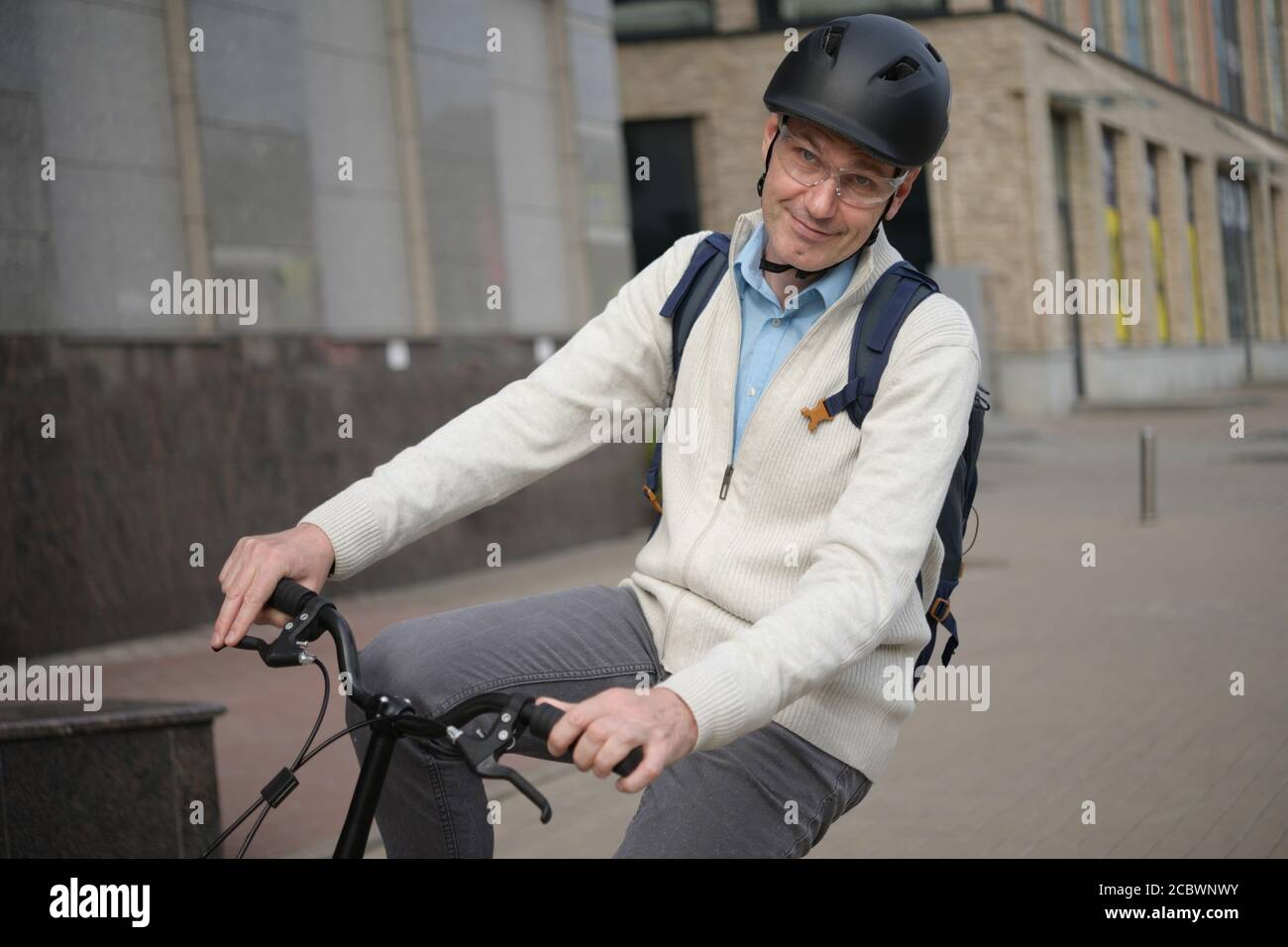 Mature Caucasian Man In A Bicycle Helmet Riding On His Bike In A City Stock Photo Alamy