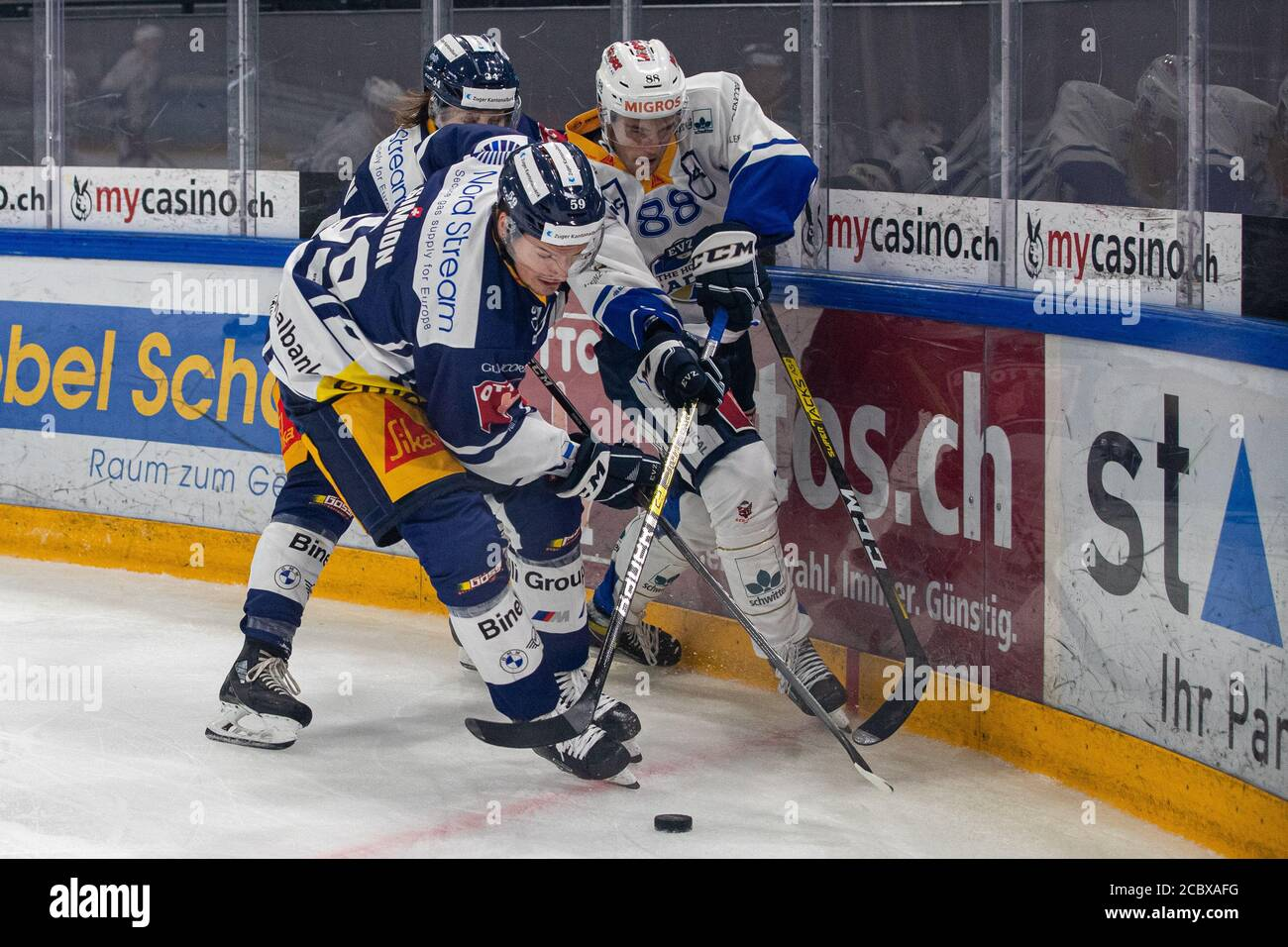 Anton Gradin # 88 (EVZ Academy) against Dario Simion # 59 (EV Zug) and Claudio Cadonau # 34 (EV Zug) during the National and Swiss League preparation ice hockey game between EV Zug and EVZ Academy on August 16, 2020 in Bossard Arena in Zug. Credit: SPP Sport Press Photo. /Alamy Live News Stock Photo