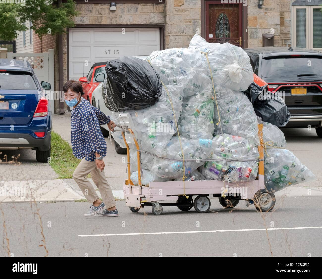 An Asian American, likely Chinese,  woman drags a huge load of deposit bottles on a wheeled cart. On 162nd St. in Flushing, Queens, New York City. Stock Photo