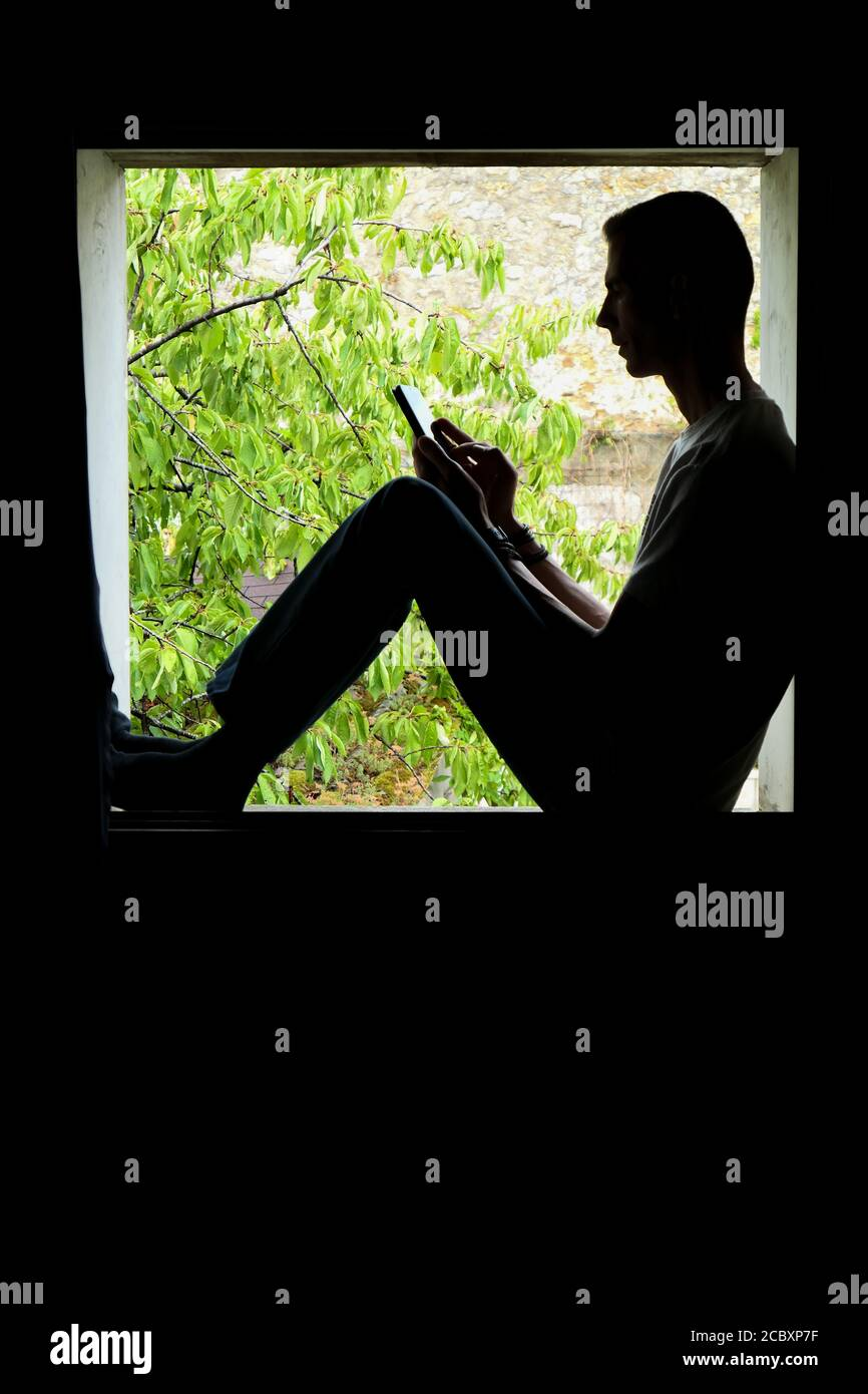 Person using technology. Silhouette of a man in the inset of a window, with a smartphone in his hands. Stock Photo