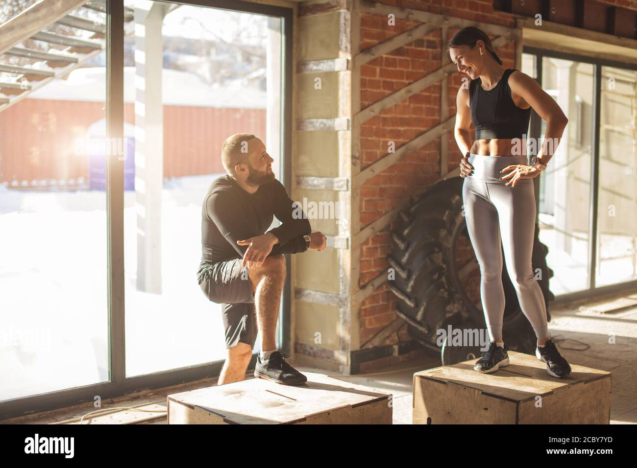 Caucasian bearded fitness coach gives advice to young smiling fit woman. SportsPeople talking friendly in a modern gym with crossfit equipment. Stock Photo