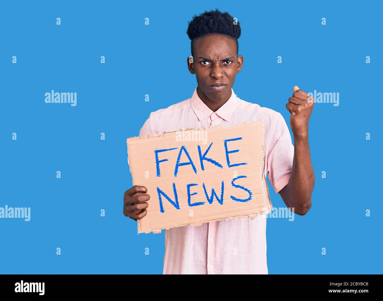 Young african american man holding fake news banner annoyed and frustrated shouting with anger, yelling crazy with anger and hand raised Stock Photo