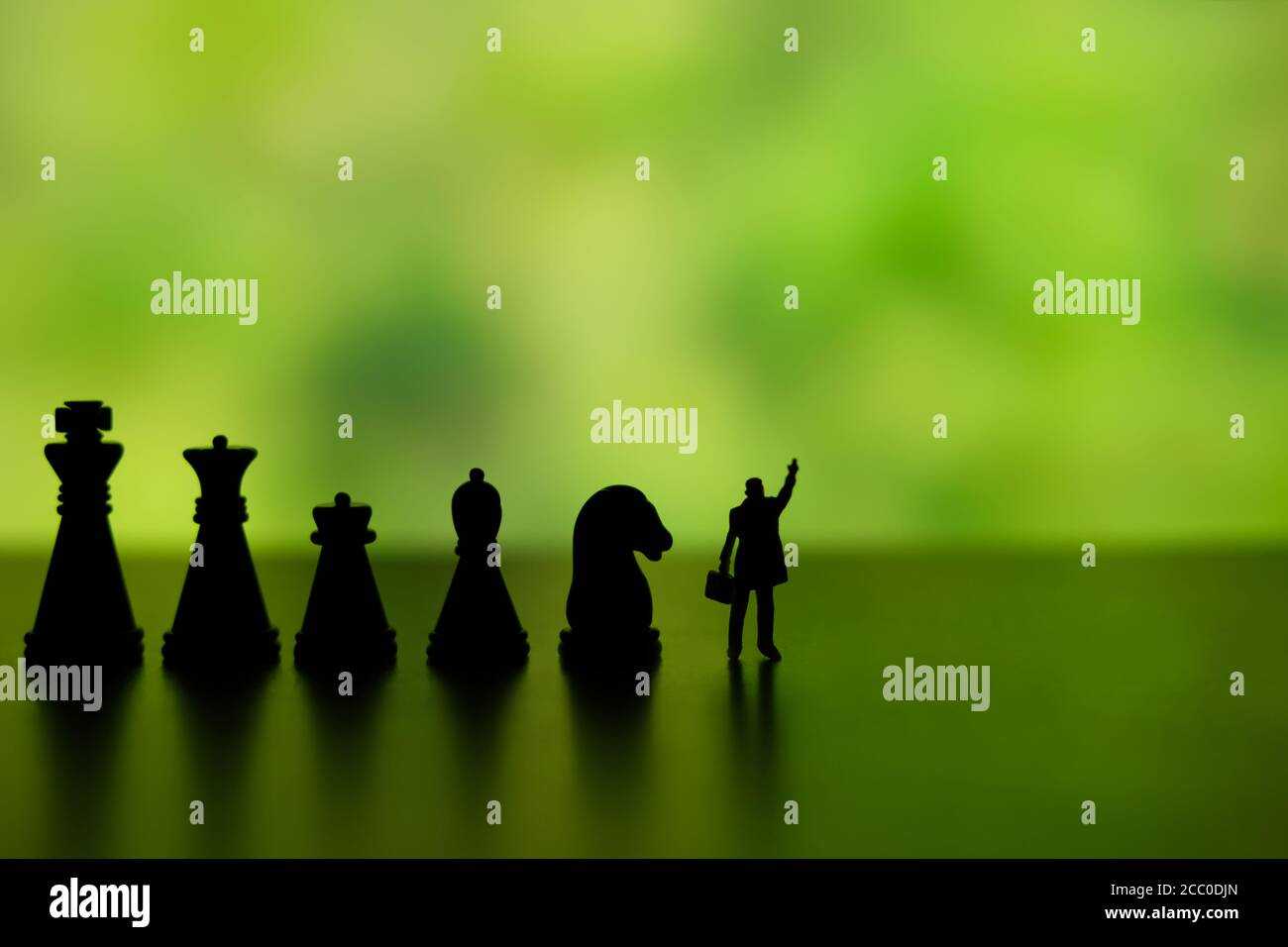 Business strategy conceptual photo - Silhouette of miniature businessman pointing upside, standing in front of chess piece row Stock Photo