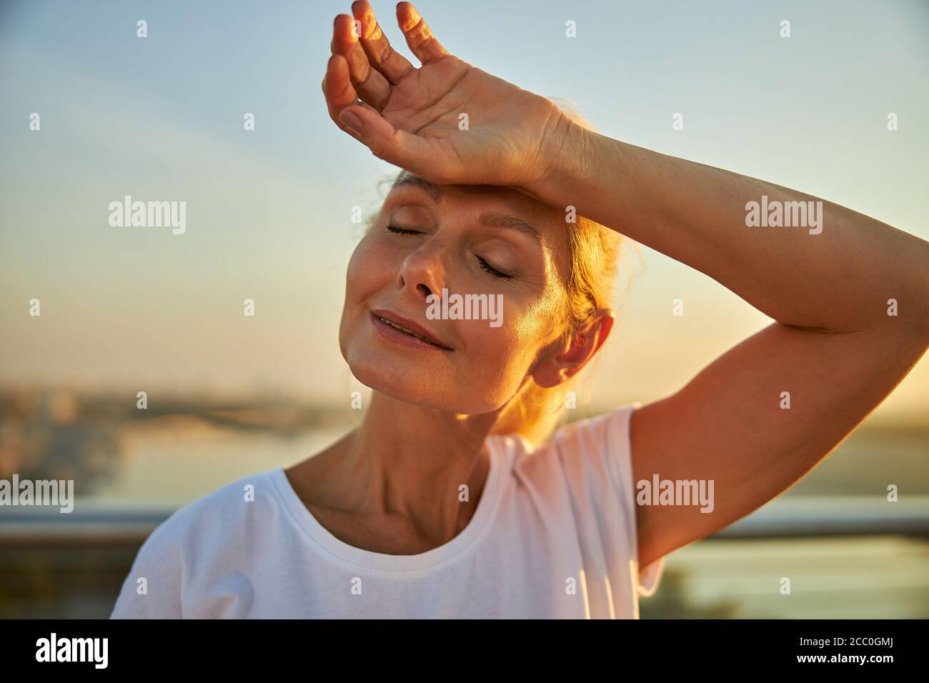 Charming woman placing hand on her forehead Stock Photo
